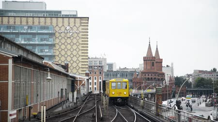 oberbaum : BERLIN - AUGUST 21: Real time locked down medium shot of a bright yellow tram arriving at the Oberbaum bridge in Berlin, Germany. Stock Footage