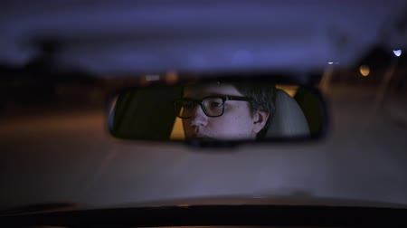 связать : Reflection of a serious young businessman s face driving his car at night. Concept of a business lifestyle. Handheld real time medium shot Стоковые видеозаписи