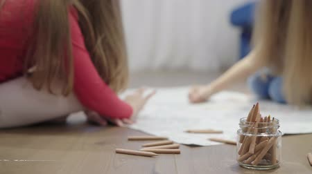 clipe de papel : Hands of unrecognizable little girls drawing a large picture on the floor with pencils. Left to right pan real time establishing shot