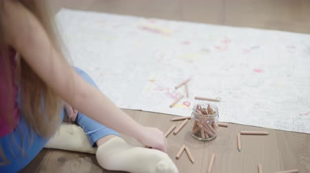 logic : Rear view of an unrecognizable little girl with long blond hair coloring a large picture while she is sitting on the floor. Left to right pan real time establishing shot Stock Footage