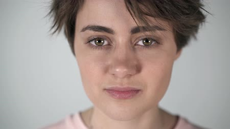 ludzie : Portrait of a young woman with short brown hair, big eyes and full lips blinking and half smiling to someone off camera. Locked down real time medium shot