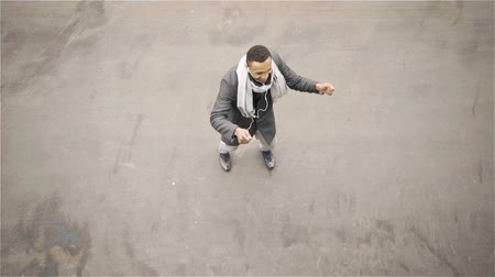 fama : Top view of a cheerful young African American man wearing a coat and a scarf dancing in an autumn street. Locked down slow motion top view shot