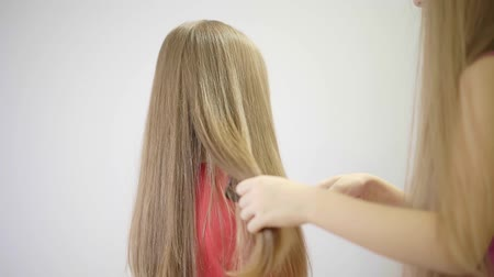 сестра : Unrecognizable little girl wearing a pink tank top is combing her sisters long blonde hair with a black comb. Concept of childhood and taking care of others. Locked down real time medium shot