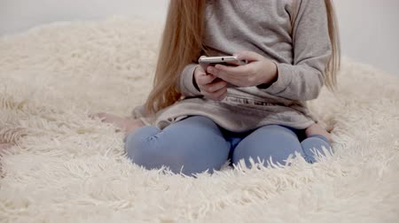 сестры : Unrecognizable little girl with long blonde hair wearing a gray dress sitting on a fluffy bed with her smartphones and web surfing. Locked down pan real time medium shot