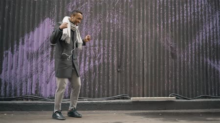 fama : Cheerful young African American man wearing a coat and a scarf dancing in an autumn street. Handheld medium shot 60FPS Stock Footage