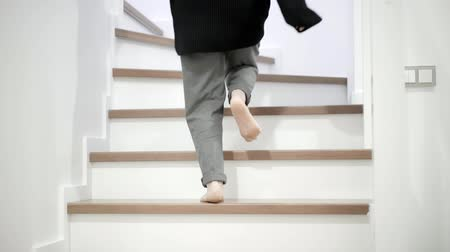 nenúfar : Unrecognizable little girl in gray pants and a sweatshirt going upstairs barefoot at home. Concept of a family life and carefree of childhood. Tilt up real time medium shot