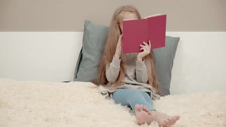 schoolkid : Left to right pan shot of a little girl wearing a gray dress and leggings reading a book sitting on a huge bed. Real time medium shot