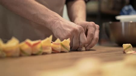 espinafre : Hands of two unrecognizable middle age men making tortellini, a traditional Italian cuisine dish. Concept of a national tradition and agriculture. Locked down real time medium shot