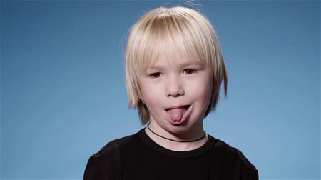 tongue : Portrait of a cute little boy with long blond hair wearing a black t shirt sticking out her tongue and smiling looking at camera. Blue background. Super slow motion locked down medium shot Stock Footage