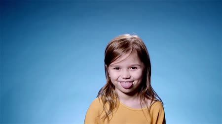 tongue out : Portrait of a cute little girl with long fair hair wearing a yellow sweater sticking out her tongue and smiling looking at camera. Blue background. Slow motion locked down medium shot