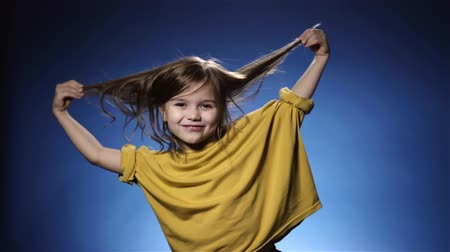 plavé vlasy : Portrait of a funny cute little girl with long dark fair hair wearing a yellow sweater playing with her hair and looking at camera. Blue background. Slow motion locked down medium shot