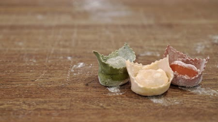 mąka : Tasty green, yellow and red tortellini lying on a wooden table in an Italian restaurant. Left to right pan real time medium shot