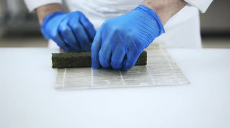 cutting mat : Hands of an unrecognizable Japanese chef forming a sushi with a bamboo mat. Making sushi and traditional Japanese cuisine concept. Locked down real time medium shot Stock Footage