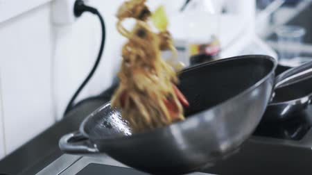 pan fried : Mushrooms, onion and chicken being fried on a pan in a restaurant kitchen by a skilled cook. Handheld real time medium shot Stock Footage