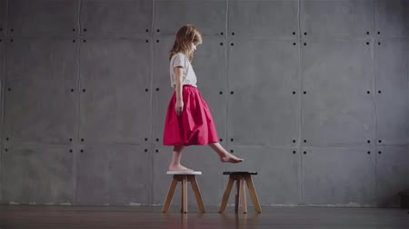 milestone : Side view of an adorable little girl wearing a pink skirt walking on small wooden chairs in a gray wall room. Locked down medium shot