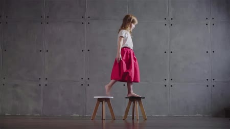 milestone : Side view of an adorable little girl wearing a pink skirt walking on small wooden chairs in a gray wall room. Locked down slow motion medium shot