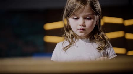 deha : Adorable pensive little girl with long dark hair wearing a white t shirt is reading a big book lying on the table. Handheld slow motion medium shot