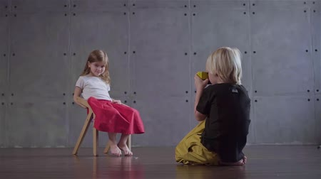 izlenim : Blond little boy sitting on the floor is taking a picture of a little girl sitting on a chair in a gray wall room. Concept of art and prodigy creative photographer. Locked down slow motion medium shot Stok Video