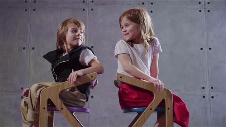 piada : Little boy and a little girl are sitting on wooden chairs back to back and laughing. Concept of humor and telling jokes. Locked down slow motion medium shot Vídeos