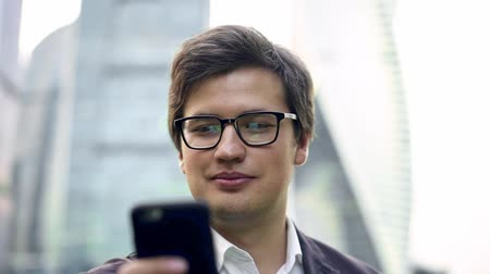 dark hair : Cheerful young businessman in glasses and a suit swiping across his smartphone screen standing against a blurred Moscow city background. Daylight. Good news concept. Slider close up shot Stock Footage