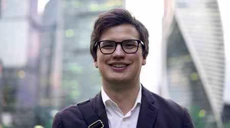 фронт : Portrait of a calm young businessman in suit and glasses looking at camera, then smiling. A Moscow city background. Summer day. Slider close up shot Стоковые видеозаписи