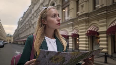 red square : Attractive tourist with blond hair looking at a map and wlaking along Tverskaya street near Kremlin Moscow, Russia. She is wearing a green jacket. Cloudy day. Tracking medium shot.