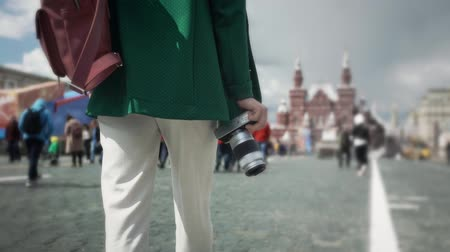red square : Rear view of a young unrecognizable woman in casual clothes walking in Moscow near Kremlin holding camera in her hand. Tourism concept. Tracking medium shot