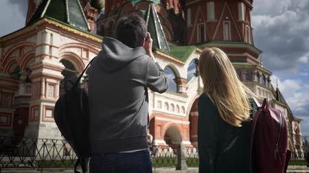 esplorare : Rear view of a young couple taking pictures of Moscow Saint Basils Cathedral, Russia. Concept of travel and tourism. Handheld medium shot