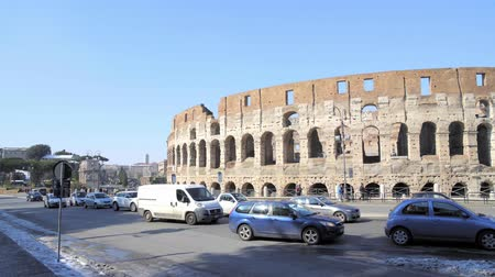 gladiatorial : ROME - FEB 20: People passing by Roman Coliseum Flavian Amphitheatre Anfiteatro Flavio Colosseo, a former gladiator arena. Cars and traffic signs, February 20, 2018. Left to right pan real time shot