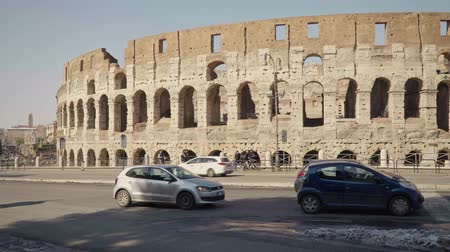 gladiatorial : ROME - FEB 20: People passing by Roman Colosseum Coliseum Flavian Amphitheatre Anfiteatro Flavio Colosseo. Cars and traffic signs. Winter day. Left to right pan real time medium shot