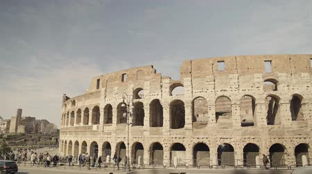 gladiatorial : ROME - FEB 20: Tourists taking pictures of Roman Coliseum Colosseo, a former gladiator arena. Blue sky with clouds, February 20, 2018 Left to right pan real time shot Stock Footage
