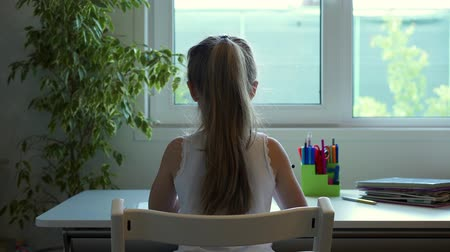 scholar : Unrecognizable little girl with long blond hair is doing her homework sitting in her room near a large window. School life concept. Slider real time medium shot Stock Footage