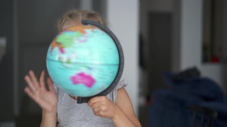 six worlds : Unrecognizable little girl wearing a white dress is whirling a globe standing in her room. Handheld real time medium shot