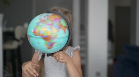 six worlds : Unrecognizable little blonde girl wearing a white dress is whirling a globe standing in her room. Slider real time medium shot