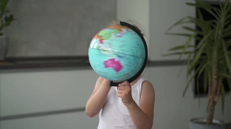 six worlds : Unrecognizable little blonde girl wearing a white dress is whirling a globe standing in her room. Handheld real time medium shot
