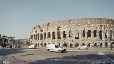 gladiatorial : ROME - FEB 20: People passing by Roman Colosseum Coliseum Flavian Amphitheatre Anfiteatro Flavio Colosseo, February 20, 2018 Cars and traffic signs. Winter day. Locked down real time establishing shot
