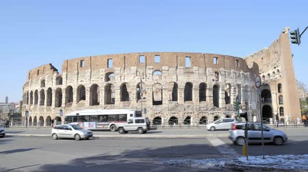 gladiatorial : ROME - FEB 20: Tourists passing by Roman Colosseum Coliseum Flavian Amphitheatre Anfiteatro Flavio Colosseo, February 20, 2018 Cars and traffic signs, day. Locked down real time establishing shot
