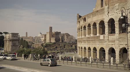 gladiatorial : ROME - FEB 20: Tourists passing by the ruins of Roman Colosseum Coliseum Flavian Amphitheatre Anfiteatro Flavio Colosseo, February 20, 2018 Vehicles, trucks. Locked down real time establishing shot Stock Footage