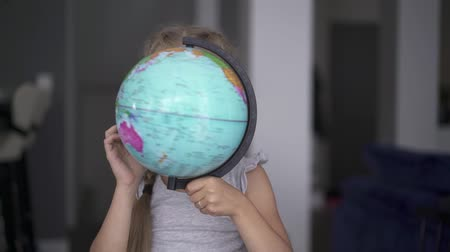 six worlds : Unrecognizable little girl wearing a white dress is whirling a globe standing in her room. Handheld slow motion medium shot