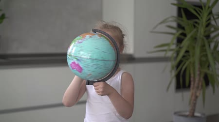 six worlds : Unrecognizable little blonde girl wearing a white dress is whirling a globe standing in her room. Handheld slow motion medium shot Stock Footage