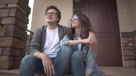 sundurma : Smiling young hipster guy in glasses is hugging his happy young wife sitting on their house porch. Family values concept. Slider slow motion medium shot Stok Video