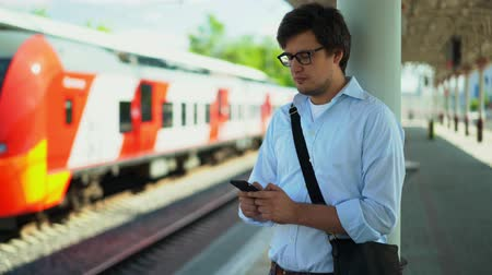 inside of train : Handsome young businessman wearing a blue shirt and glasses is texting while standing on the platform waiting for his train. Sunny summer day. Handheld real time medium shot