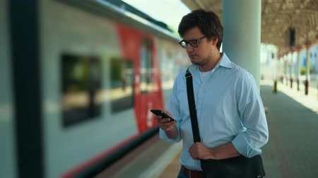 inside of train : Young businessman wearing a blue shirt and glasses is texting while standing on the platform waiting for his train. Sunny summer day. Handheld real time medium shot Stock Footage