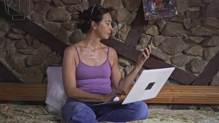 munkaruha : Middle aged asian woman wearing jeans typing on laptop sitting on sofa at home, answering her smartphone and talking. Left to right pan real time medium shot
