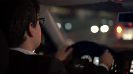 accent : Nape of businessman dressed in a black suit wearing eyeglasses driving a car in the night city switching a lane moving to the left side, hand held shot