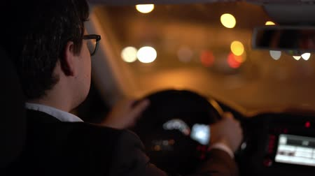 steering wheel : Nape of businessman dressed in a black suit wearing eyeglasses driving a car in the night his hands on the wheel, hand held shot