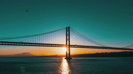 brug : Zonsondergang op de 25 de Abril Bridge in Lissabon timelapse Stockvideo
