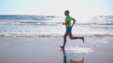 Adult Man in Shorts with a T-shirt Jogging on Ocean Beach, slow motion