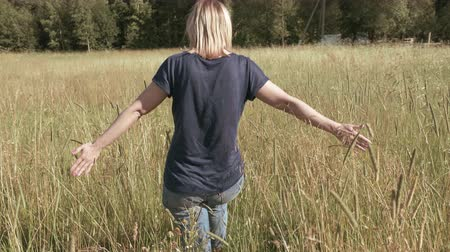 slowing : The shooting took place in the field, in the estate in the Rostov region, Russia. In the frame of the girl, seen from behind, is on the field with both hands gently touches the top of the grass