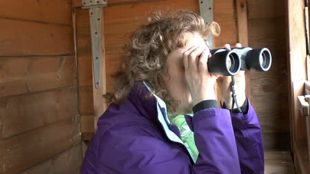 bird learning : Female bird watcher using a pair of binoculars in a hide looking at birds Stock Footage